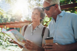 Close up portrait of senior couple using a map for directions. Retired couple exploring new places to visit during their vacation.