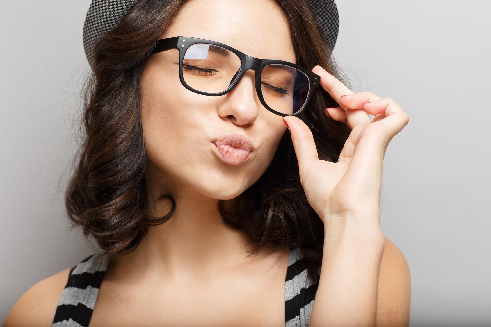 Schönes attraktives Mädchen in einem Hut und Brille.